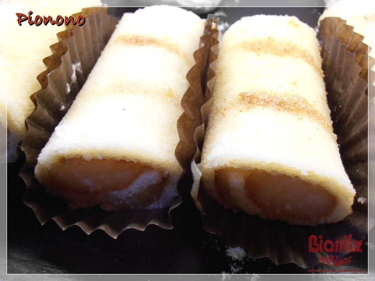 Pionono bañado en chocolate crujiente. Pionono: Rollo dulce de bizcocho relleno de crema , cubieto con azúcar y canela. Su nombre viene del papa Pío IX (Pio nono).